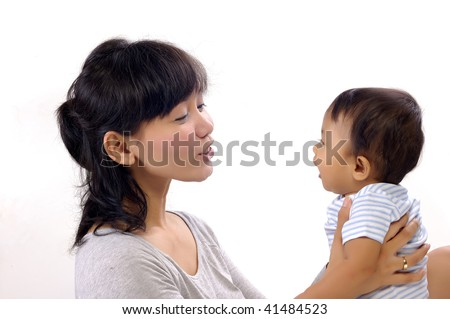 Happy mother with cute baby girl in the studio. Mother teaching the baby to talk - stock photo