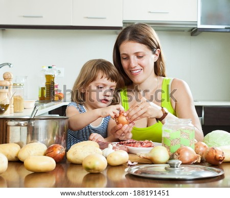 Happy mother with daughter cooking with groats at home - stock photo