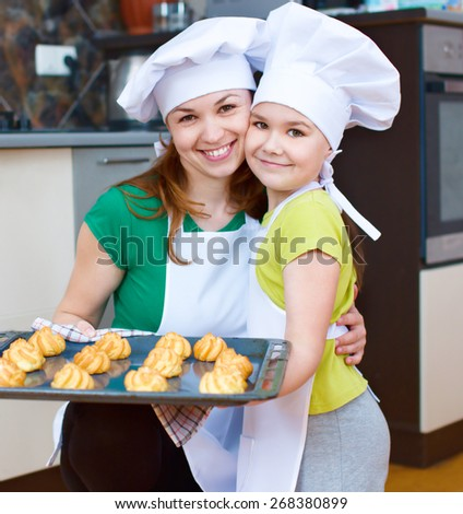 Happy mother with daughter making bread in the kitchen - stock photo
