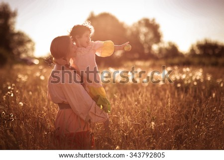 happy mother with daughter on the hands in a wheat field, family in a wheat field On the Sunset, look forward - stock photo