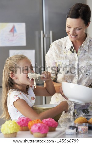 Happy mother with daughter tasting cupcake batter in kitchen