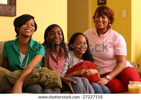 Happy mother with daughters at home. Shallow DOF, focus on the girl in front. - stock photo