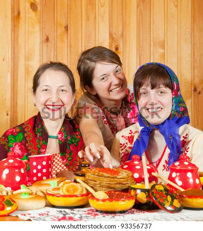 Happy mother with  daughters eating pancake with caviare during  Shrovetide