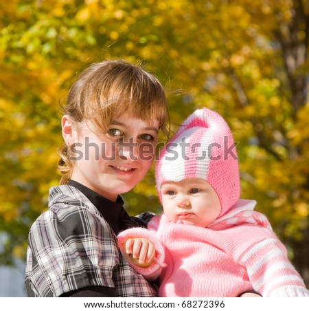 Happy mother with her baby against autumn nature - stock photo