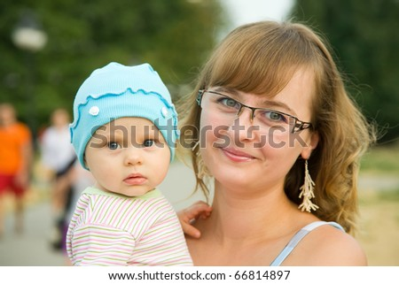 Happy mother with her baby against city park - stock photo