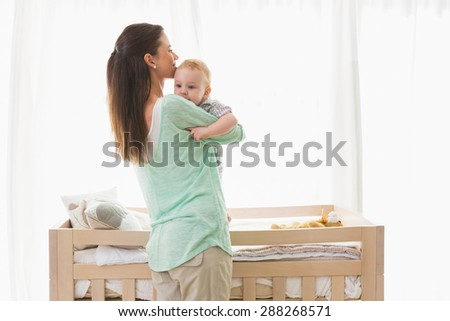Happy mother with her baby boy at home in bedroom - stock photo