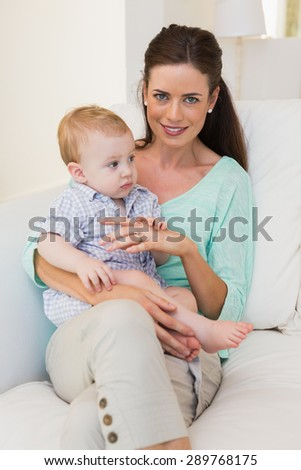 Happy mother with her baby boy at home in the living room - stock photo