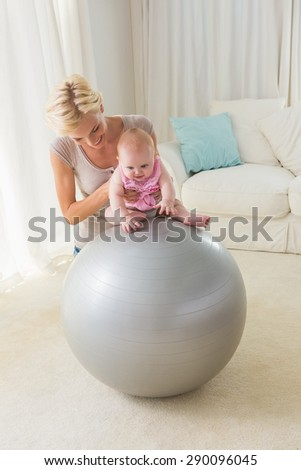 Happy mother with her baby girl on the exercice ball at home in the living room - stock photo