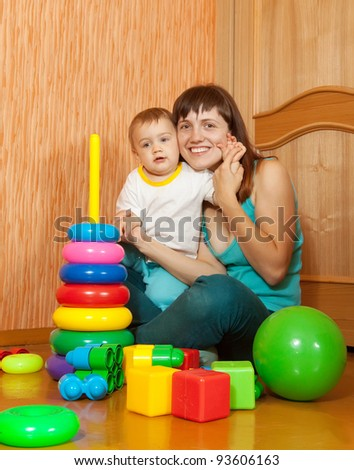 Happy mother with her baby in interior - stock photo