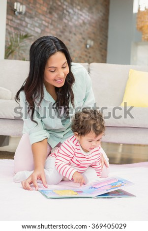 Happy mother with her baby looking at a book on the carpet in living room - stock photo