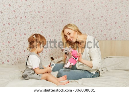 happy mother with her child in room. playing on sofa with toys - stock photo