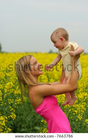 Happy mother with her child in yellow flowers field - stock photo