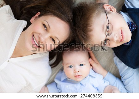 Happy mother with her children having fun on floor of in living room at home, laughing - stock photo
