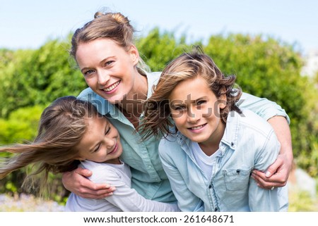 Happy mother with her children in the countryside - stock photo