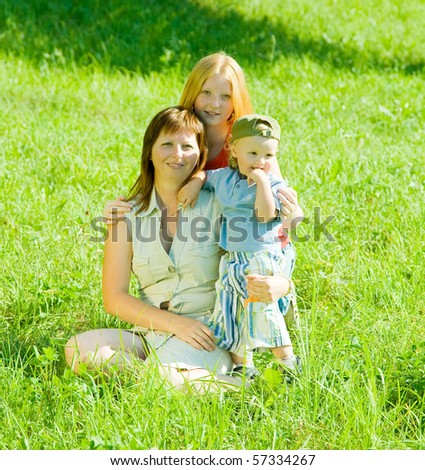 Happy mother with her children  sit in grass - stock photo