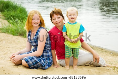 Happy mother with her children sit on sand - stock photo