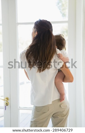 Happy mother with her cute baby girl look out at home - stock photo