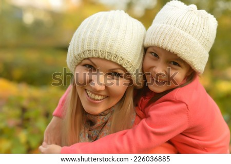 Happy mother with her cute daughter in autumn park