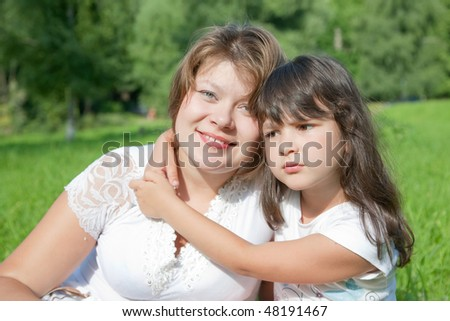 Happy mother with her daughter against nature