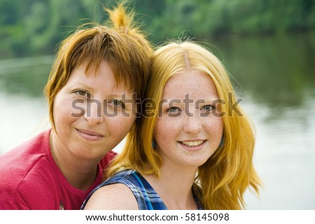 Happy mother with her daughter against nature - stock photo