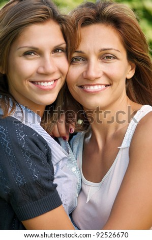 Happy mother with her daughter in park outdoors - stock photo