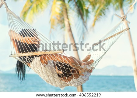 happy mother with her daughter lying in a hammock on the shore of a tropical beach. Mothers day.  - stock photo