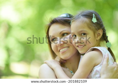 Happy mother with her daughter walk in summer park - stock photo