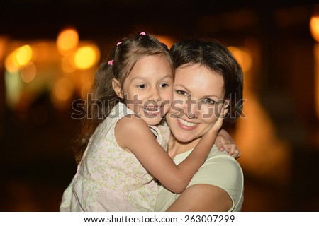 Happy mother with her daughter walk in summer park at night - stock photo