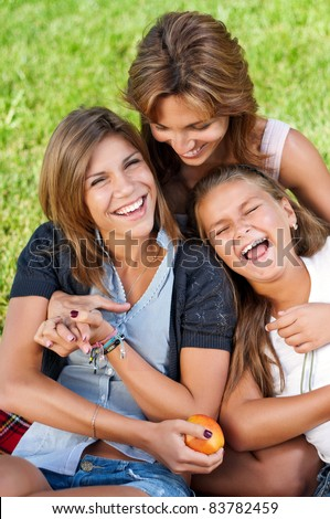 Happy mother with her daughters in park outdoors - stock photo