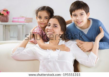 Happy mother with her little children at home - stock photo