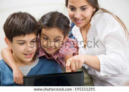 Happy mother with her little children with laptop at home - stock photo