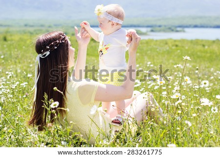 Happy mother with her little daughter are wearing white clothes and wreath playing on the meadow with chamomile flowers - stock photo