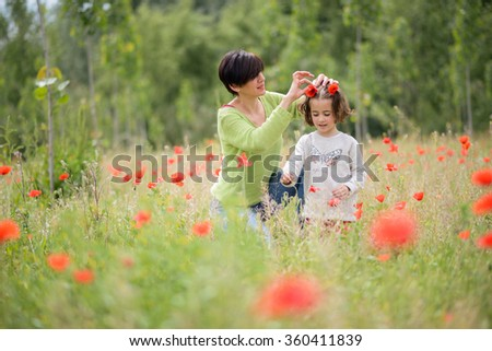 Happy mother with her little daughter in poppy field - stock photo