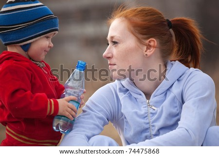 Happy mother with her son  against nature - stock photo