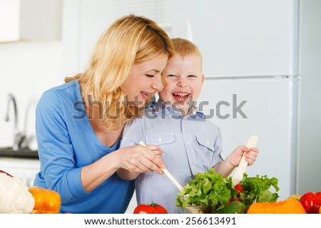 Happy mother with her son having fun in the kitchen - stock photo