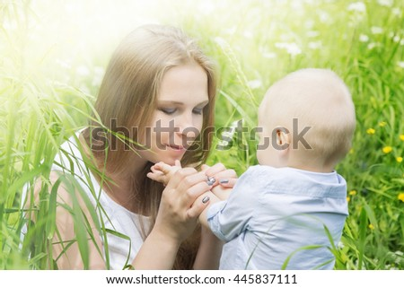 Happy mother with her son in a meadow - stock photo