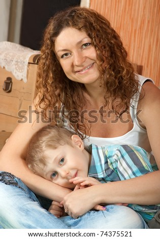 Happy mother with her son  in interior - stock photo