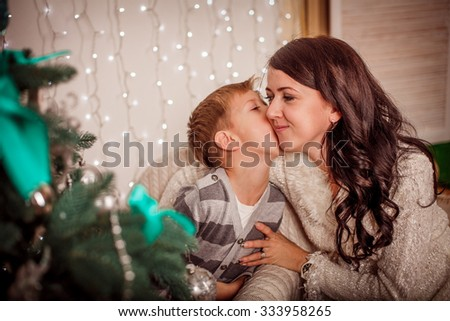 Happy mother with her son near Christmas tree - stock photo