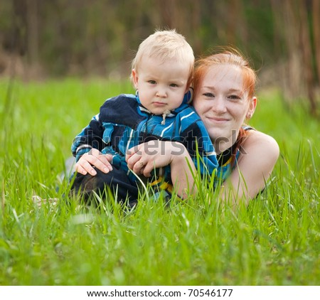 Happy mother with her son on meadow - stock photo
