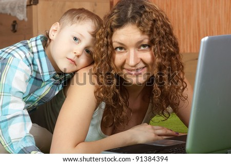 Happy mother with her son  on sofa with notebook - stock photo