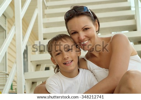 Happy mother with her son on stairs - stock photo