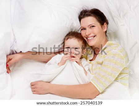 happy mother with her son on white bed, shot from above - stock photo