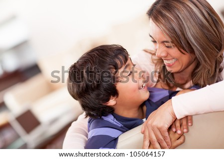 Happy mother with her son smiling at home