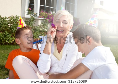 Happy mother with her sons, birthday party in garden. Outdoor photo. - stock photo