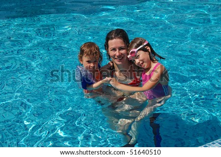 Happy mother with her two kids in the swimming pool - stock photo