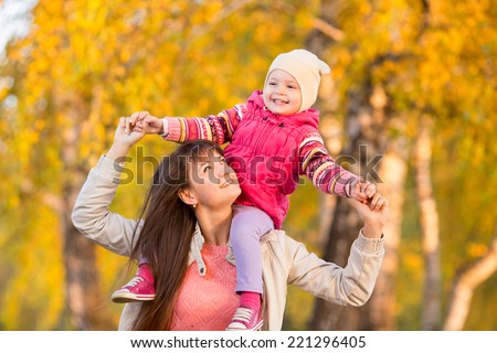happy mother with kid girl walking outdoors over autumnal background - stock photo