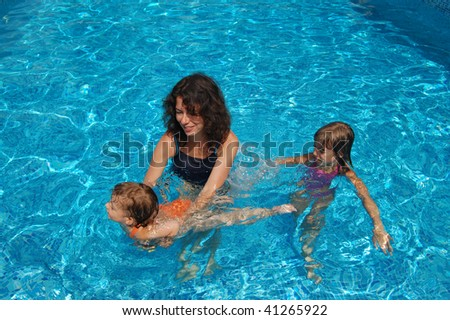 Happy mother with kids in swimming pool - stock photo