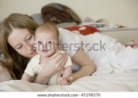 happy mother with little baby lying on bed