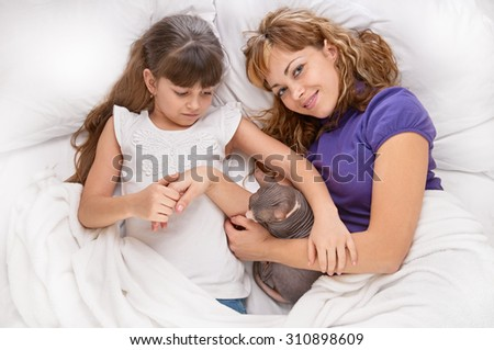 happy mother with little daughter and cat sphynx on white bed, shot from above - stock photo