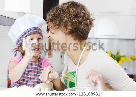 Happy mother with little daughter joyful cooking - stock photo